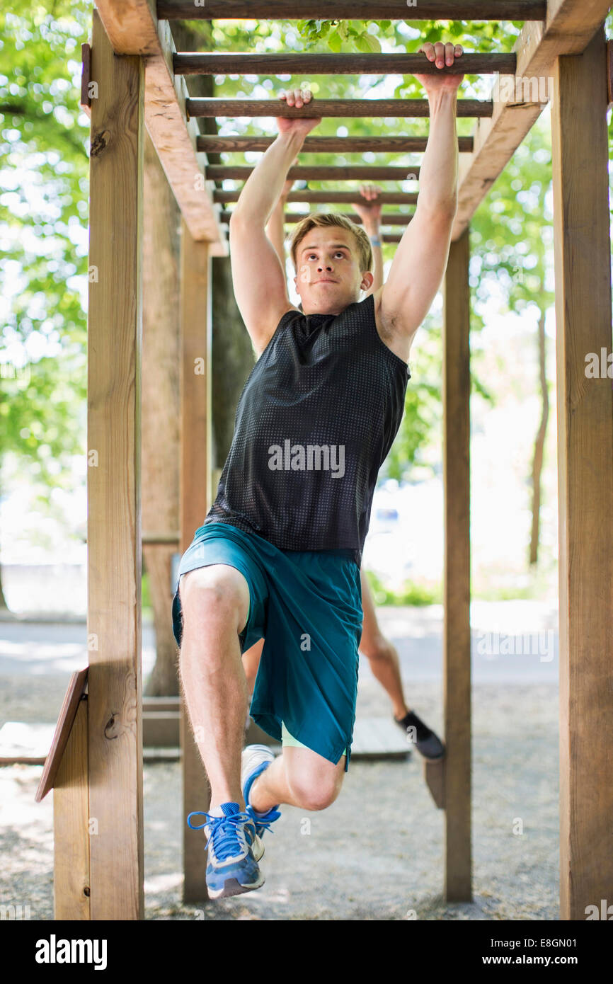 Full length of determined man hanging on monkey bars at outdoor gym - Stock Image