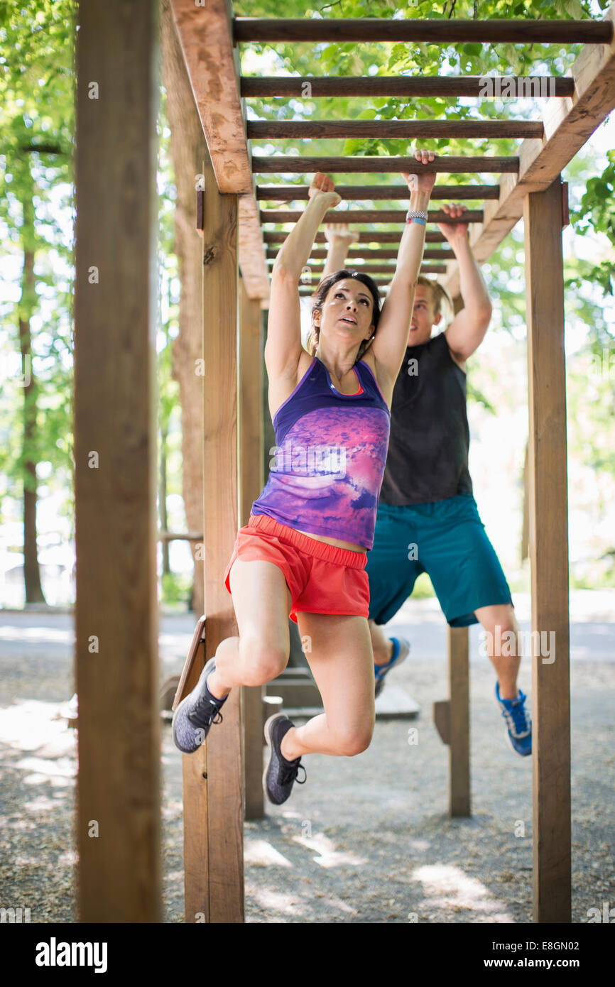 Determined couple hanging on monkey bars at outdoor gym - Stock Image