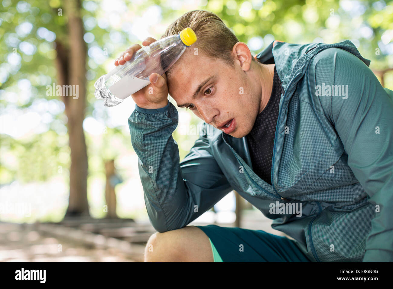 Tired man panting while holding water bottle after workout at park - Stock Image