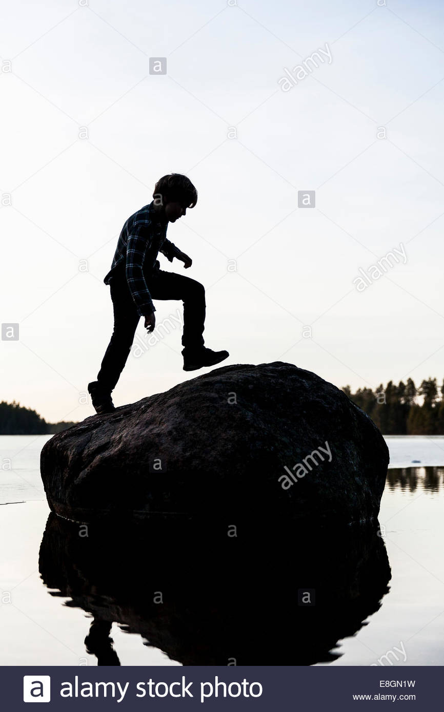 Full length of boy moving up rock against clear sky - Stock Image