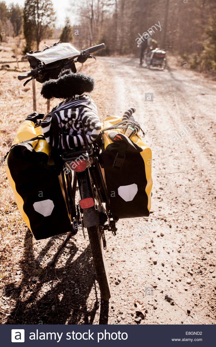 Luggage tied to bicycle parked on dirt road with family in background - Stock Image