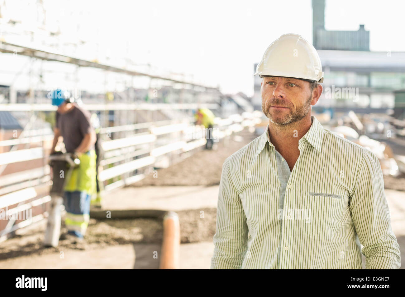 Architect looking away while standing at construction site - Stock Image