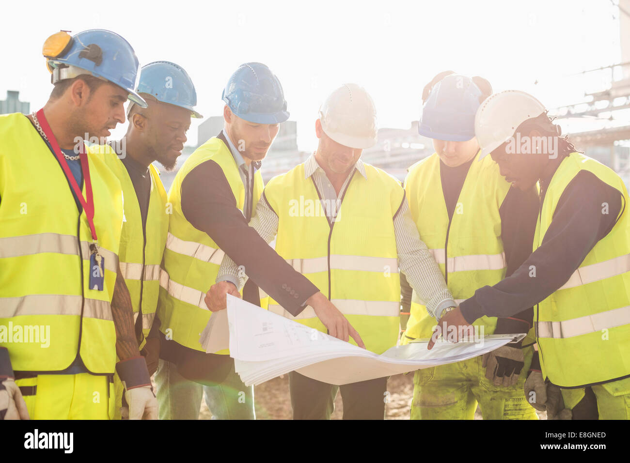 Architect explaining plan on blueprint to construction workers at architect explaining plan on blueprint to construction workers at site malvernweather Image collections