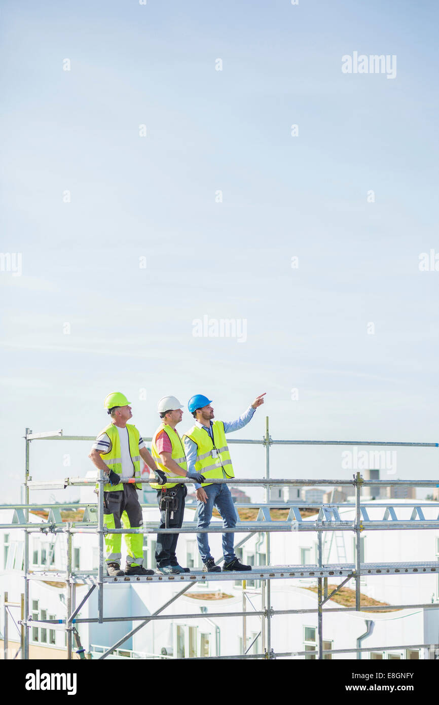 Architect showing something to colleagues while standing on scaffolding against sky - Stock Image