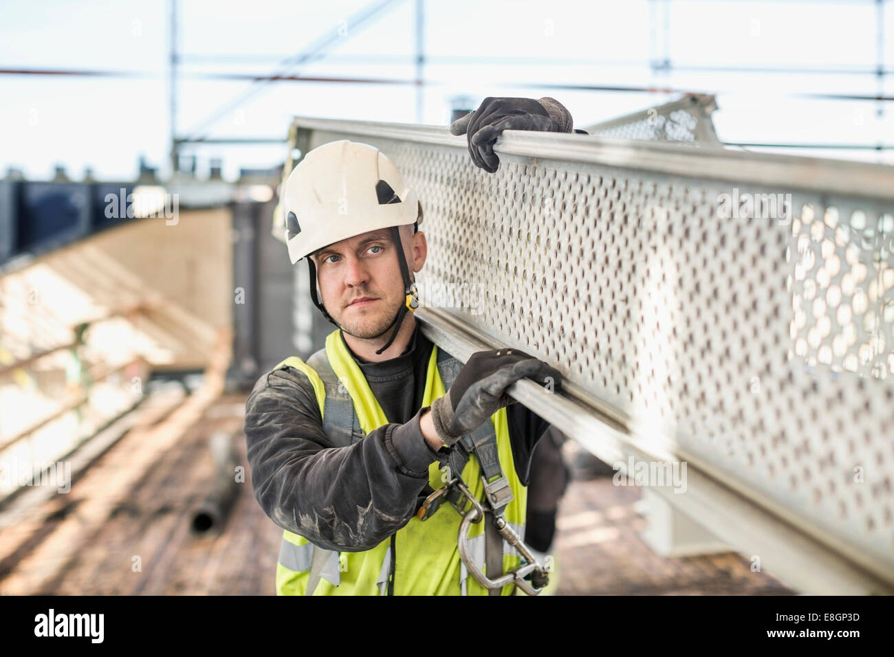 Construction worker looking away while carrying metal plank at site - Stock Image