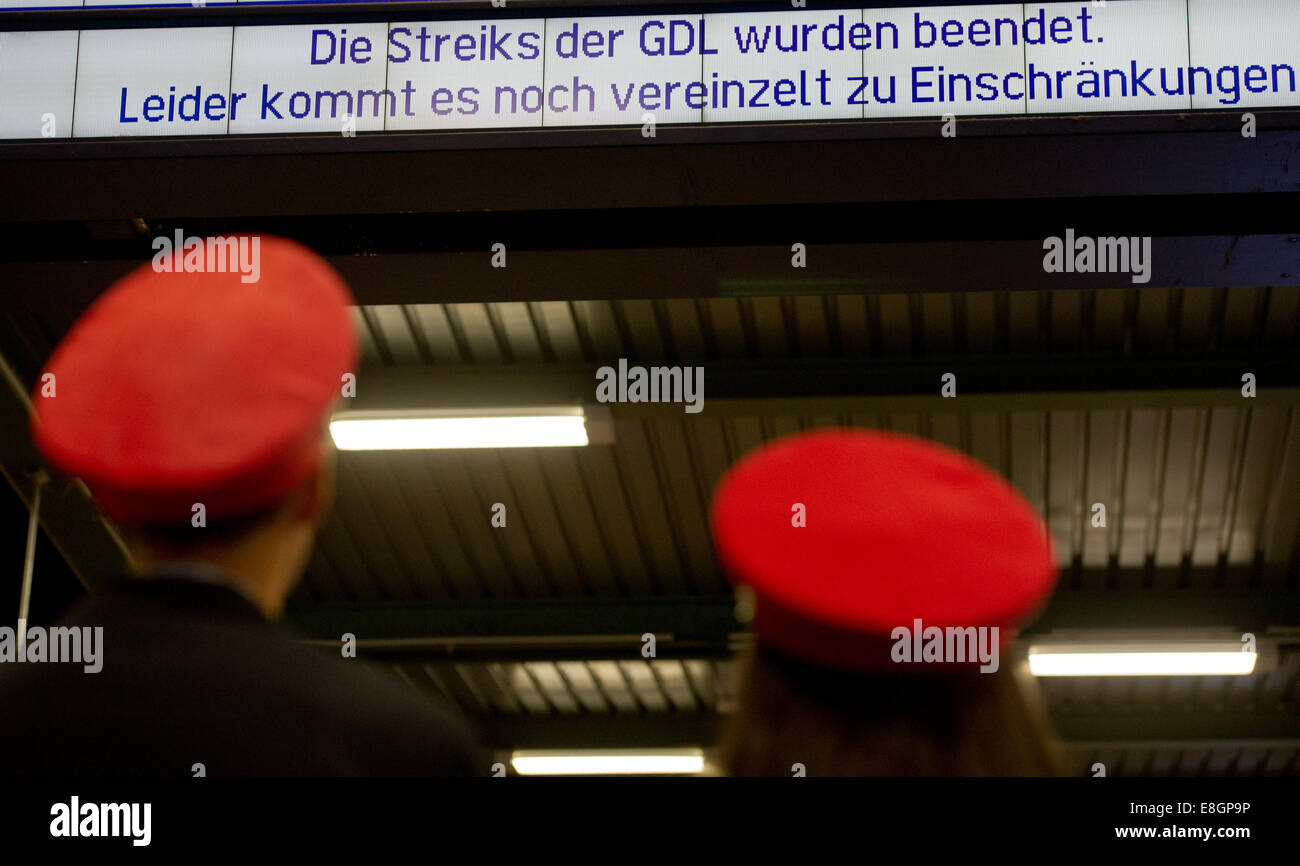 Two employees of the Deutsche Bahn stand before display panel reading 'GDL strikes are over. Unfortunately there - Stock Image