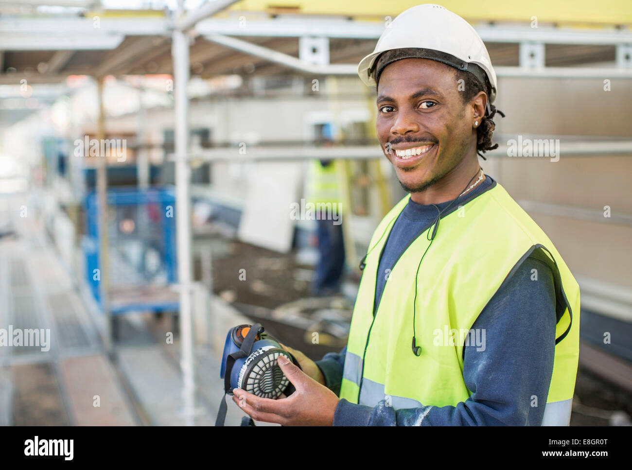 Portrait of happy worker at construction site - Stock Image