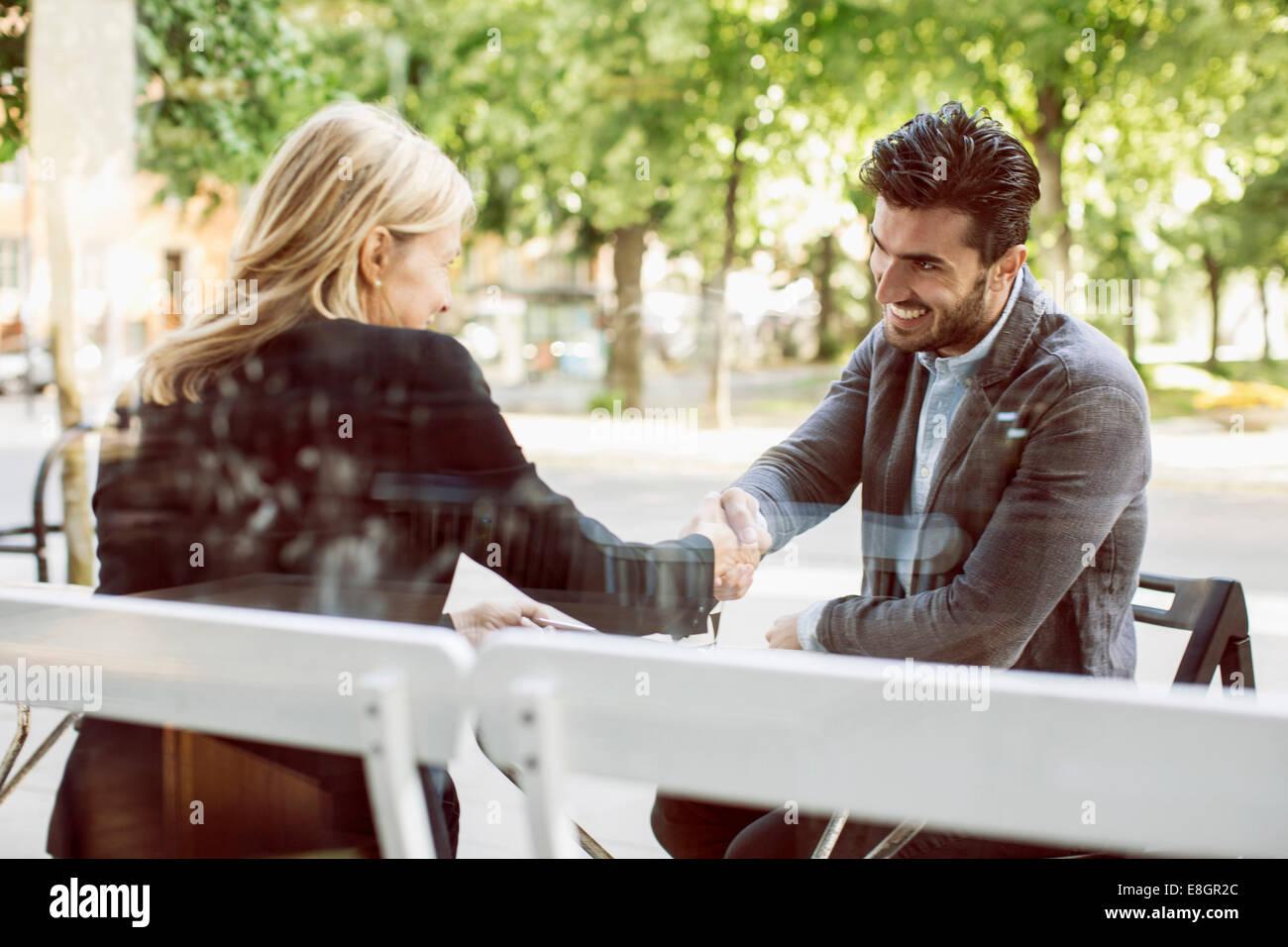 Business partners shaking hands at sidewalk cafe - Stock Image