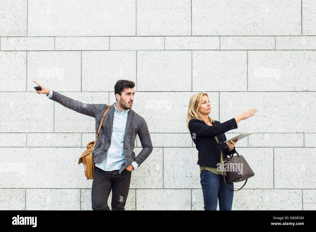 Business colleagues pointing opposite directions against wall outdoors - Stock Image