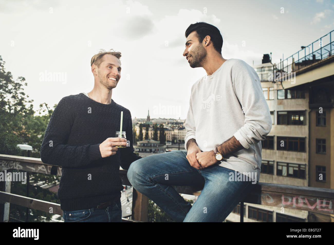 Happy male friends communicating on roof garden - Stock Image