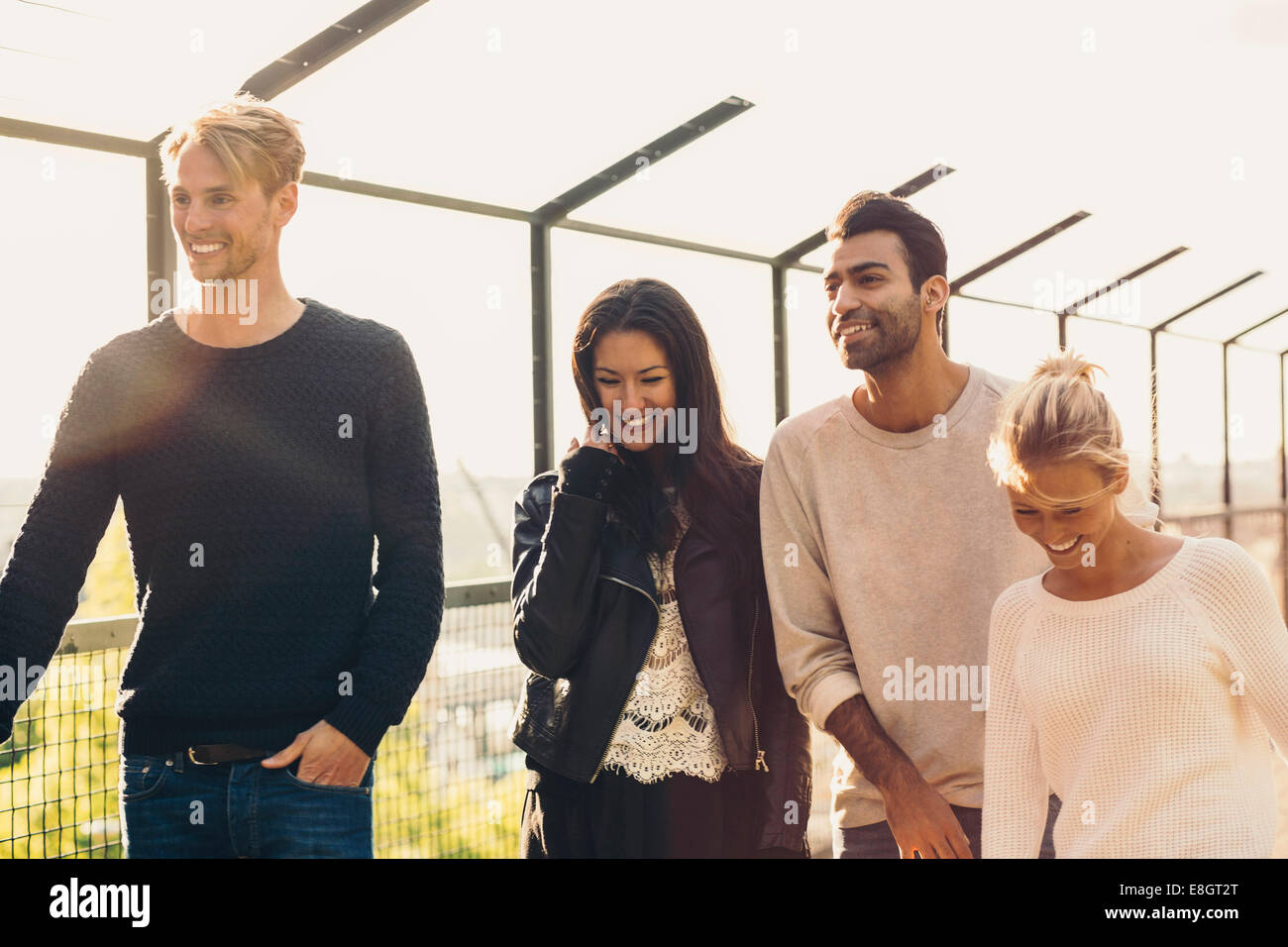 Happy multi-ethnic friend walking outdoors - Stock Image