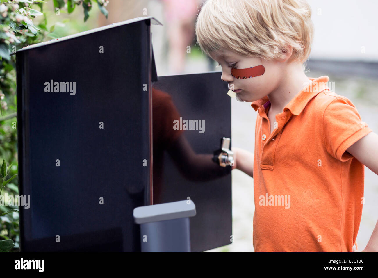 Boy looking into letter box outdoors - Stock Image
