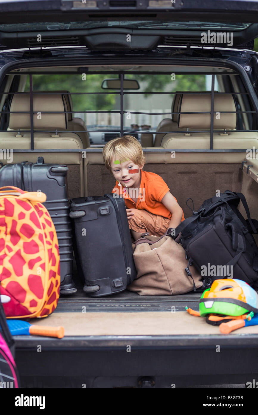 Boy sitting with luggage in car trunk - Stock Image