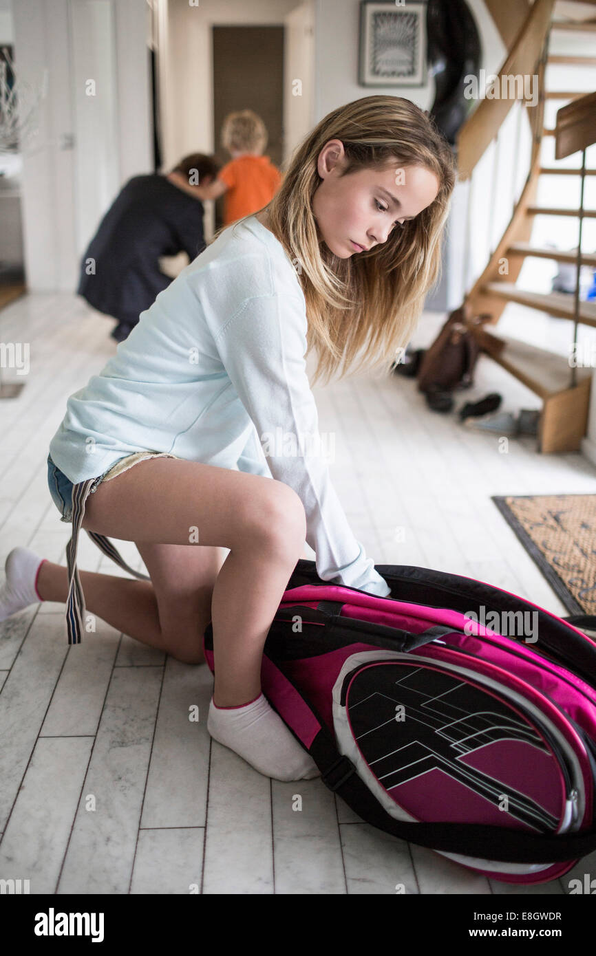 Girl packing badminton bag at home with family in background - Stock Image