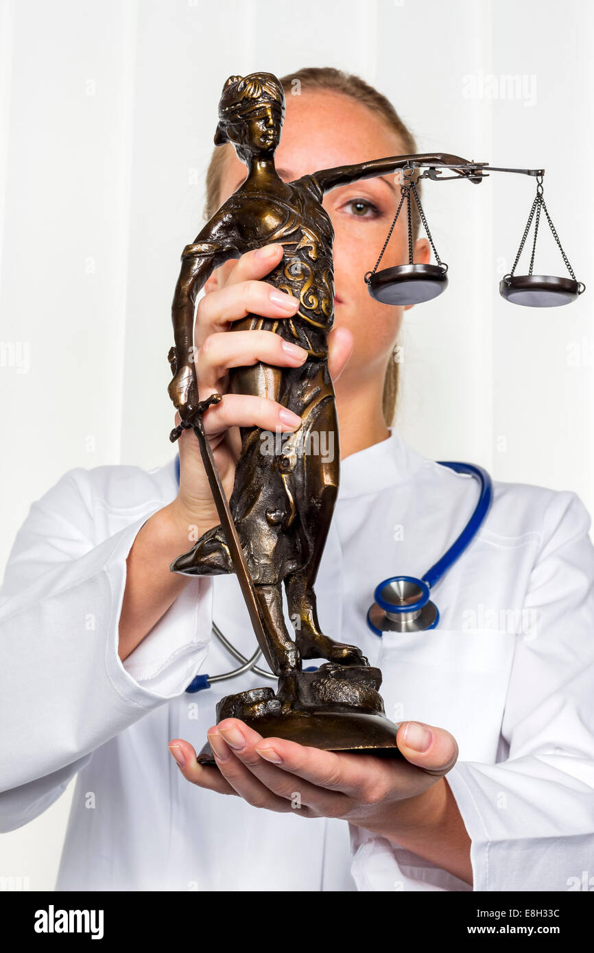 Doctor holding Lady Justice figurine Stock Photo