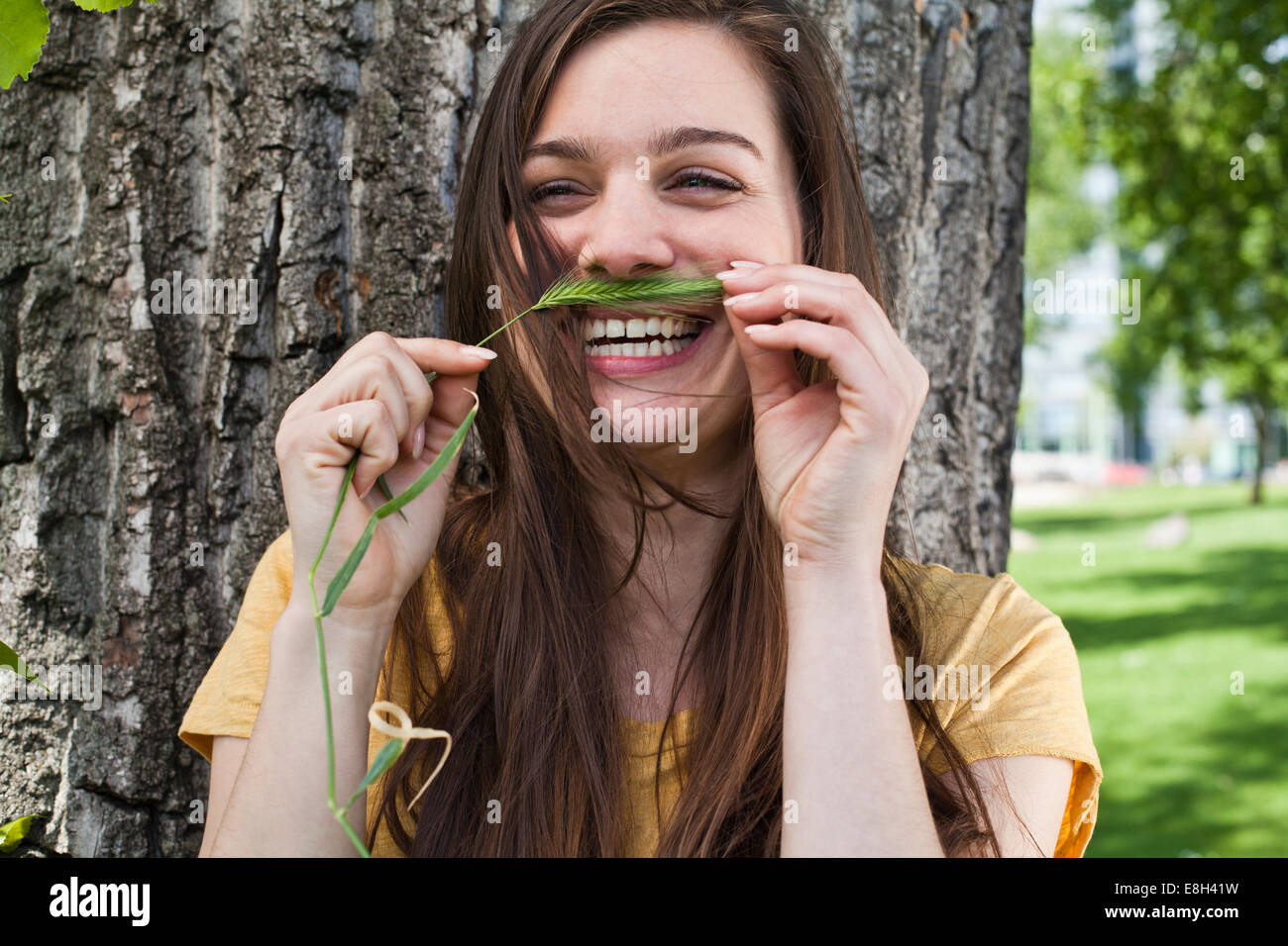 Portrait of young woman holding spike in her face like a moustache - Stock Image