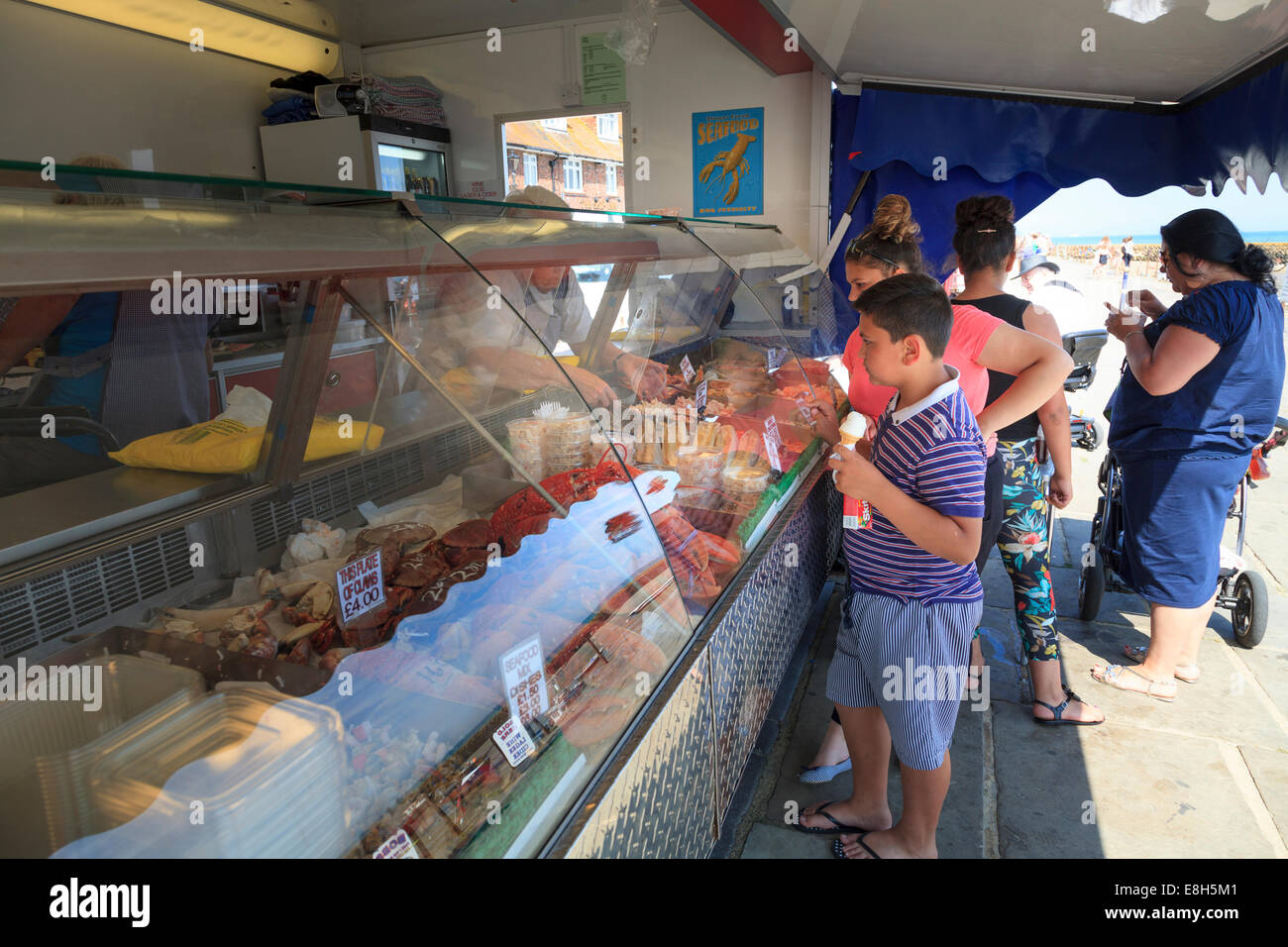 Young boy holding ice cream choosing fresh fish from a stall. - Stock Image