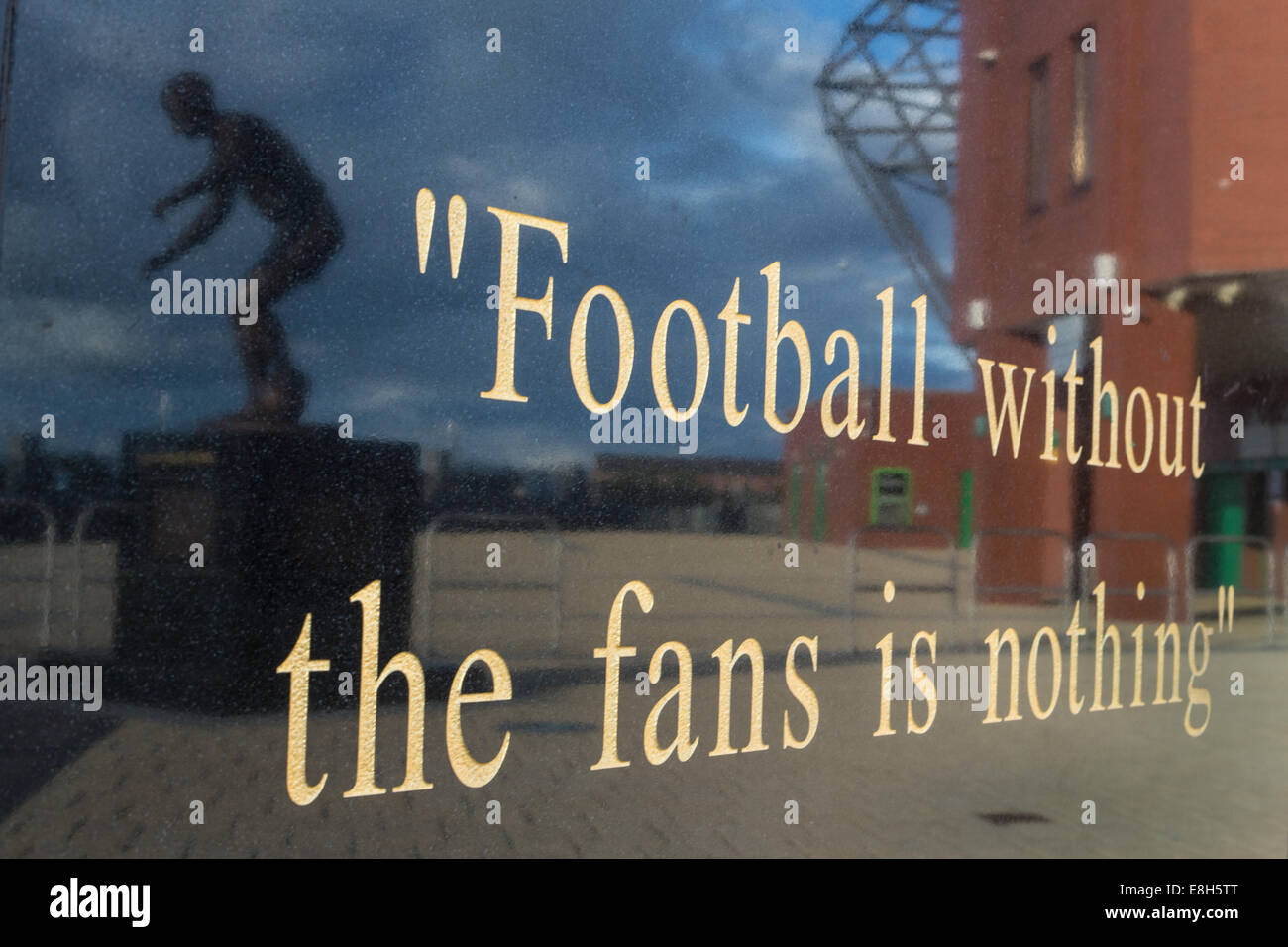 Quote from former manager Jock Stein on a statue's plinth, with reflection of statue of former player and legend - Stock Image