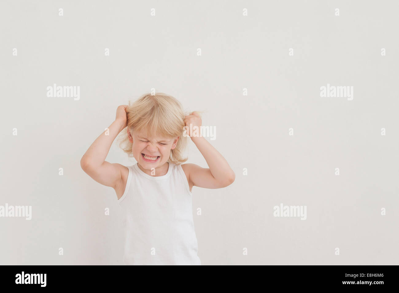 Portrait of angry little boy tearing his hairs - Stock Image