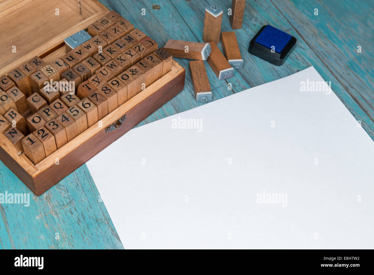 Sheet of white paper, wooden box of wooden letter stamps and an ink pad Stock Photo