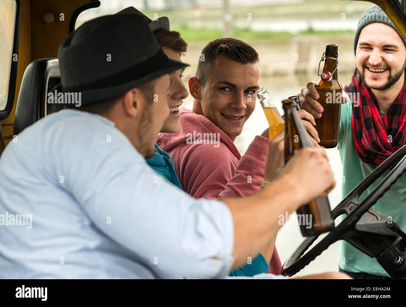 Group of friends drinking beer in car - Stock Image