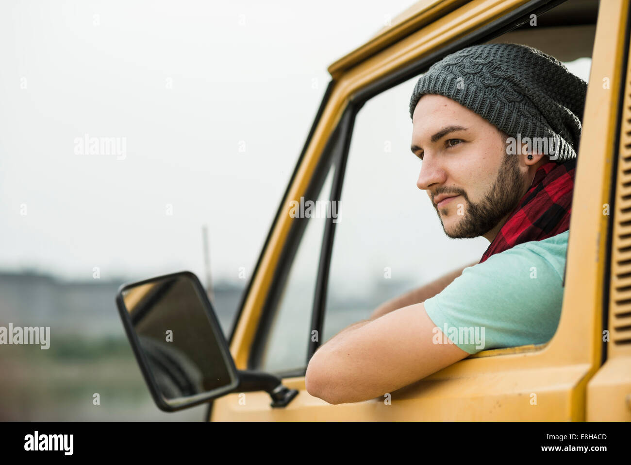 Young man sitting in pick-up truck looking out of window - Stock Image