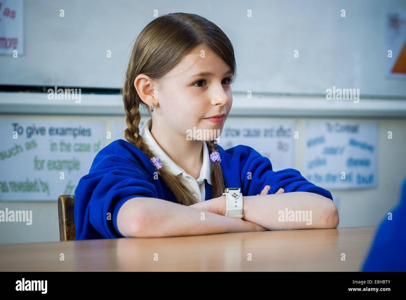 Primary school girl at desk in classroom,UK - Stock Image
