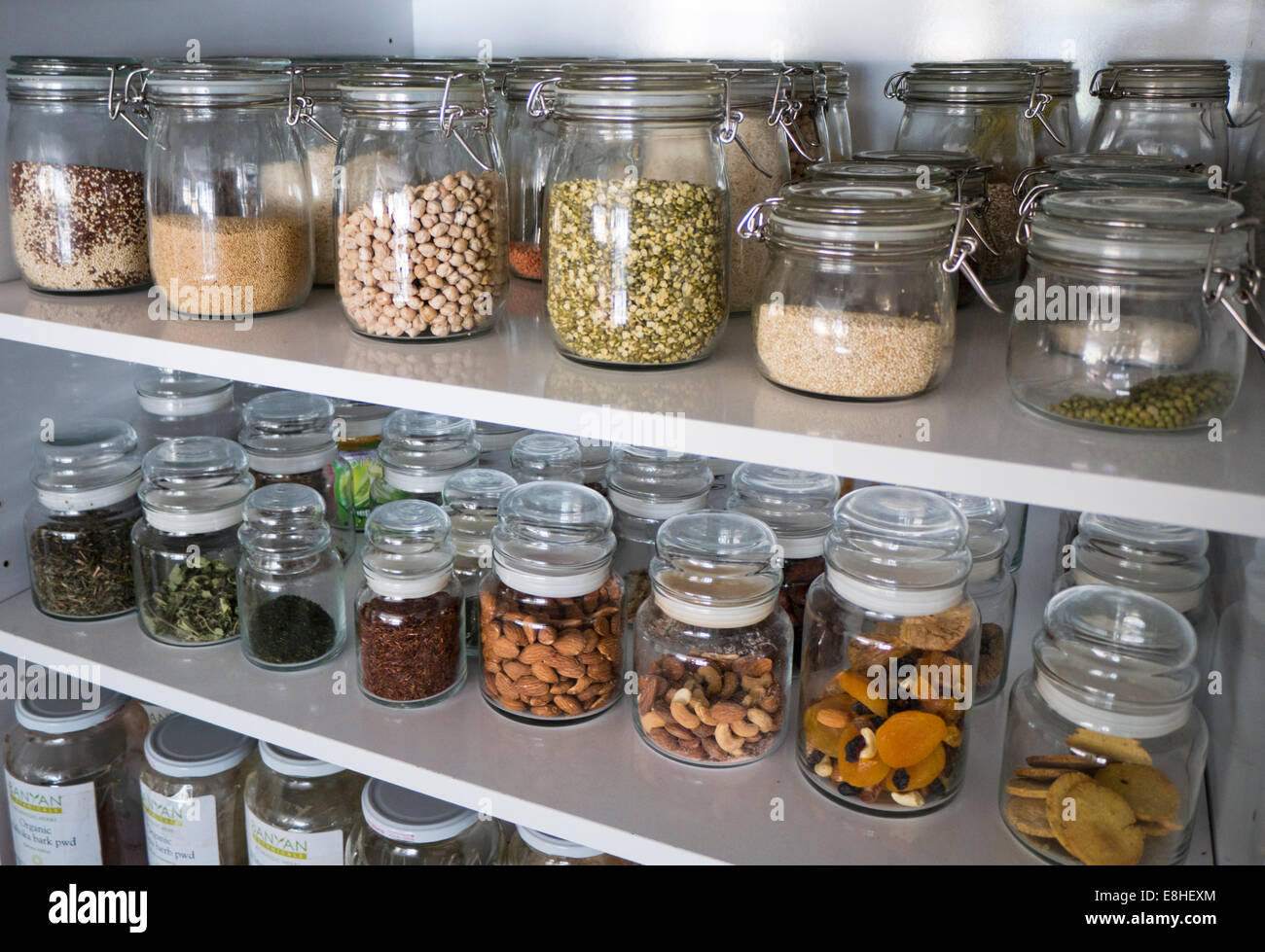 Storage Jars Containing Dried Nuts, Pulses And Fruit On A Shelf In A Kitchen