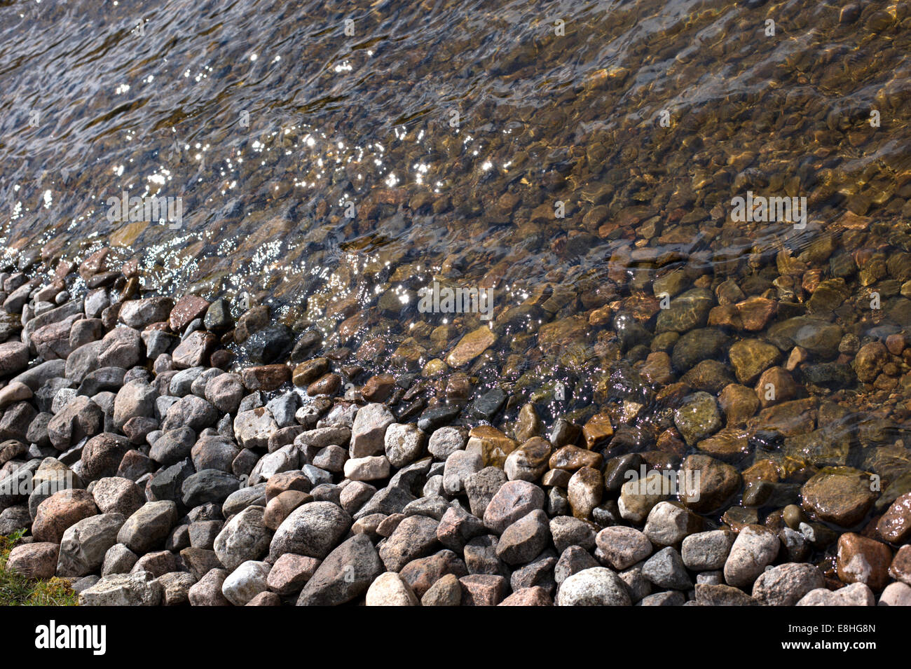 Sunlight on the water in close up as the gentle waves on Loch Builg lap the rocky shoreline - Stock Image