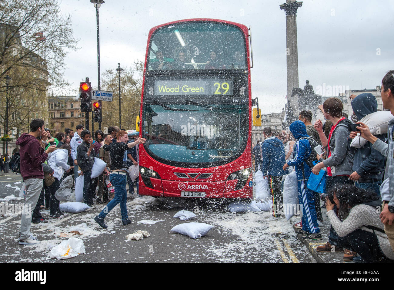 A bus drives through the commotion as Londoners pillow fight in the street around Trafalgar Square during International - Stock Image