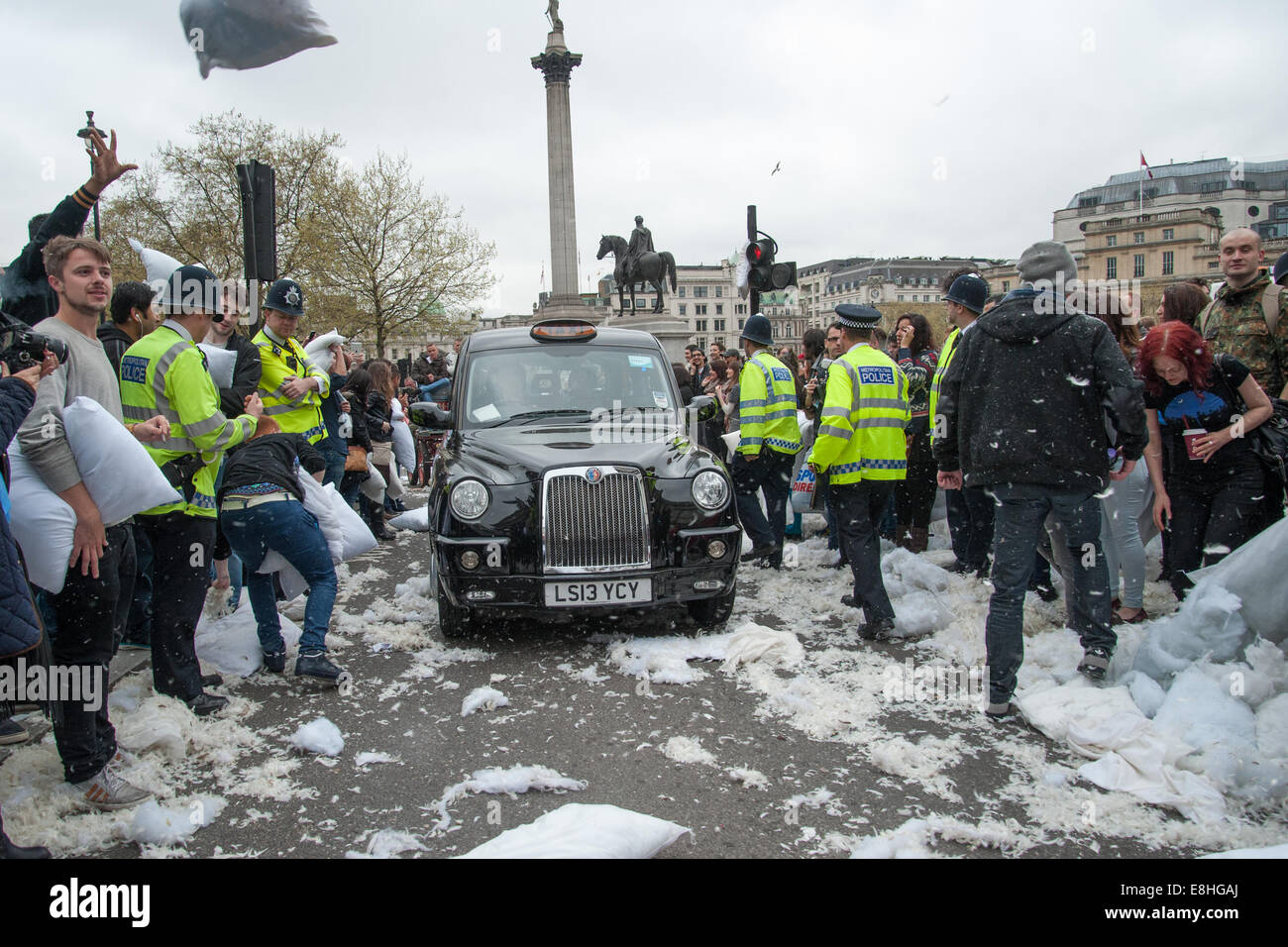 A taxi drives through the commotion as Londoners pillow fight in the street around Trafalgar Square during International - Stock Image