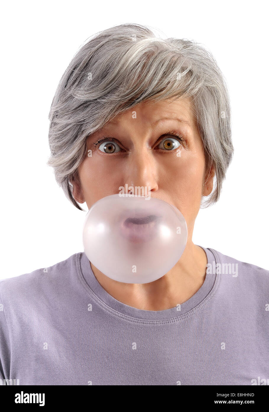 Adult Woman with Short Gray Hair Blowing Chewing Gum with Eyes Wide Open Looking at Camera. Isolated on White Background. - Stock Image