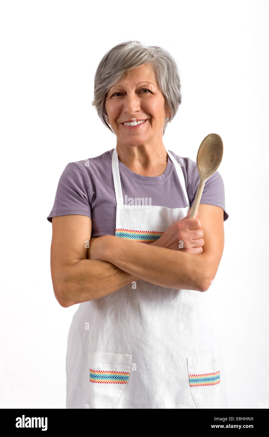 Senior lady with a wooden spoon - Stock Image