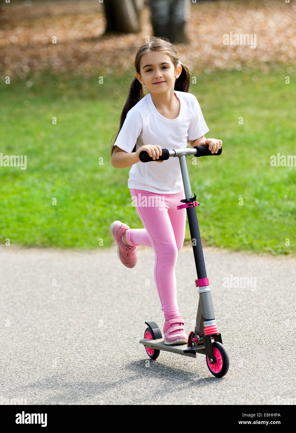 Cute young girl in pink with her brown hair in pigtails playing on a push scooter outdoors on a road having fun - Stock Image