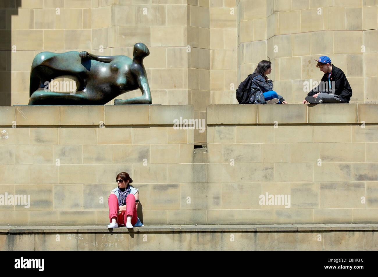 Leeds, UK. People relaxing in the sun next to the Henry Moore sculpture 'Reclining Woman' outside the Leeds Art Stock Photo