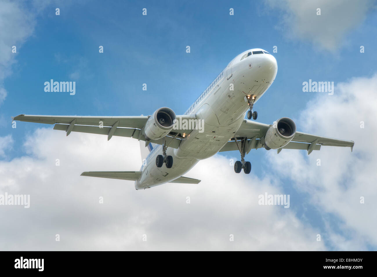 big jet plane taking off on blue cloudy sky nackground - Stock Image