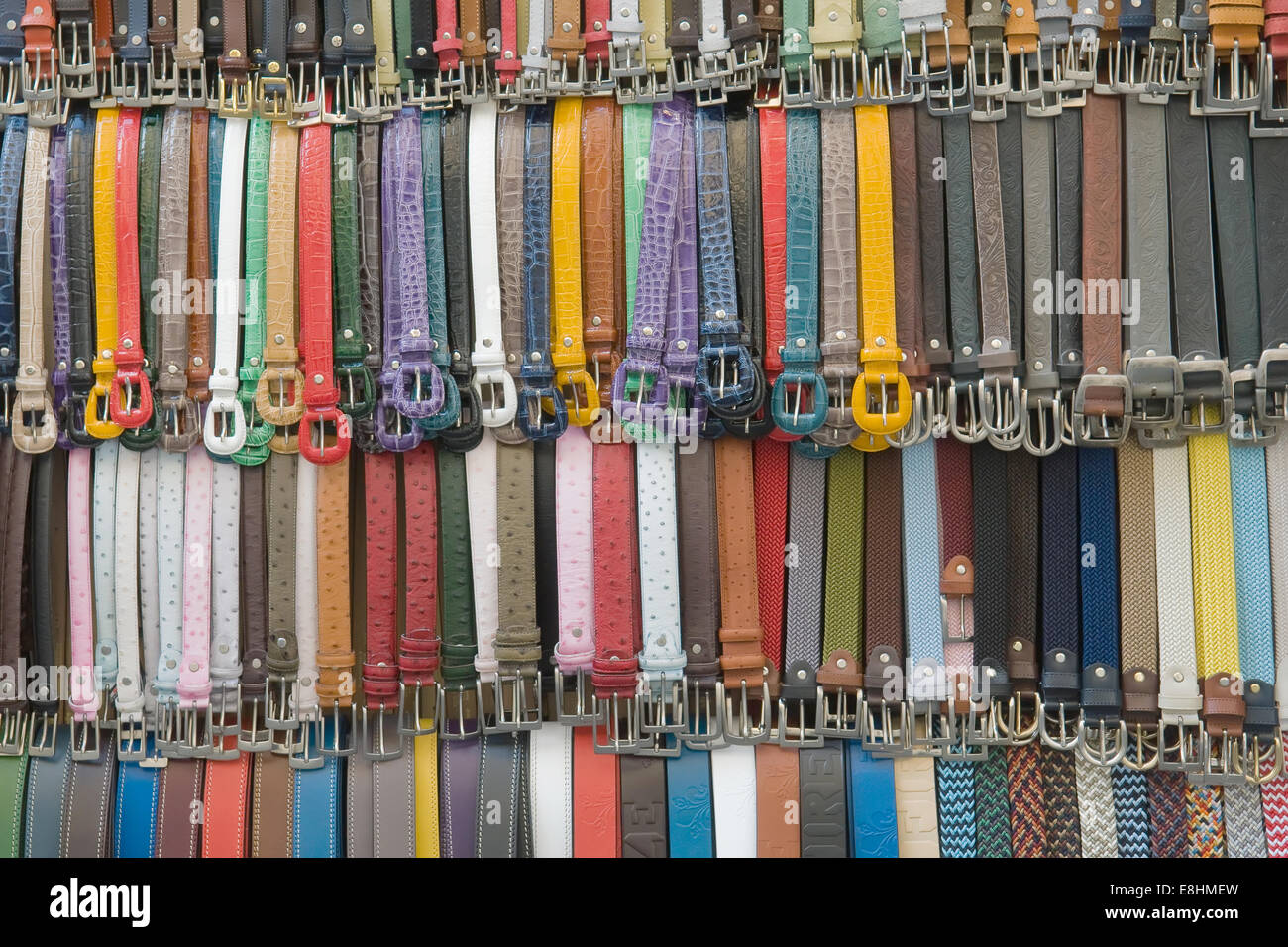 many colored leather belts on a market - Stock Image