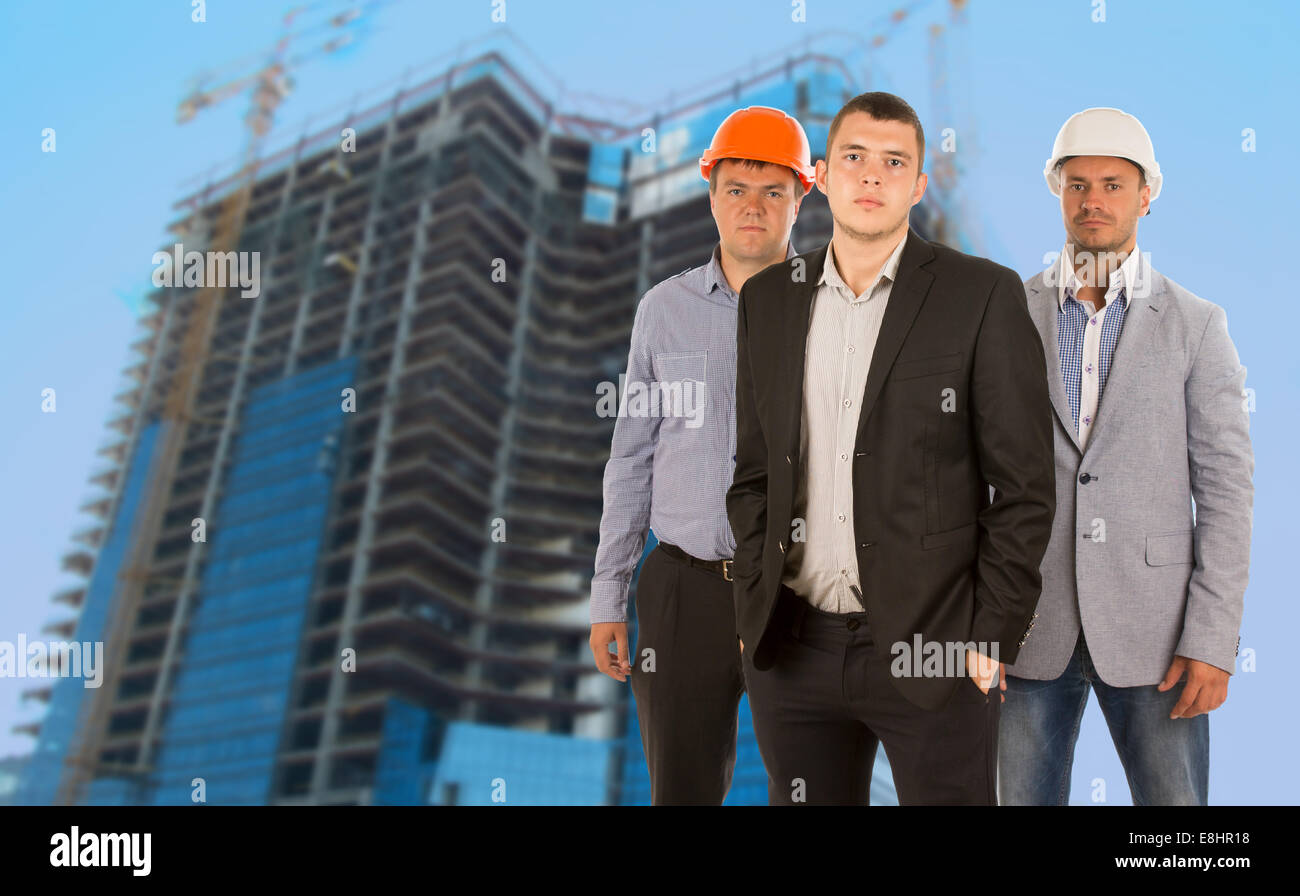 Group of three engineers and architects in their hardhats standing grouped in front of a skyscraper under construction - Stock Image