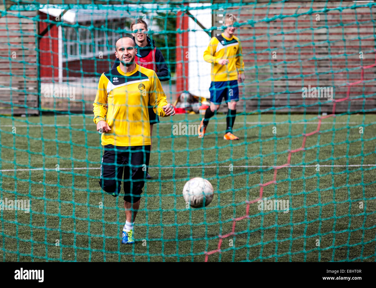 Young men playing football (soccer) in Seydisfjordur Iceland - Stock Image