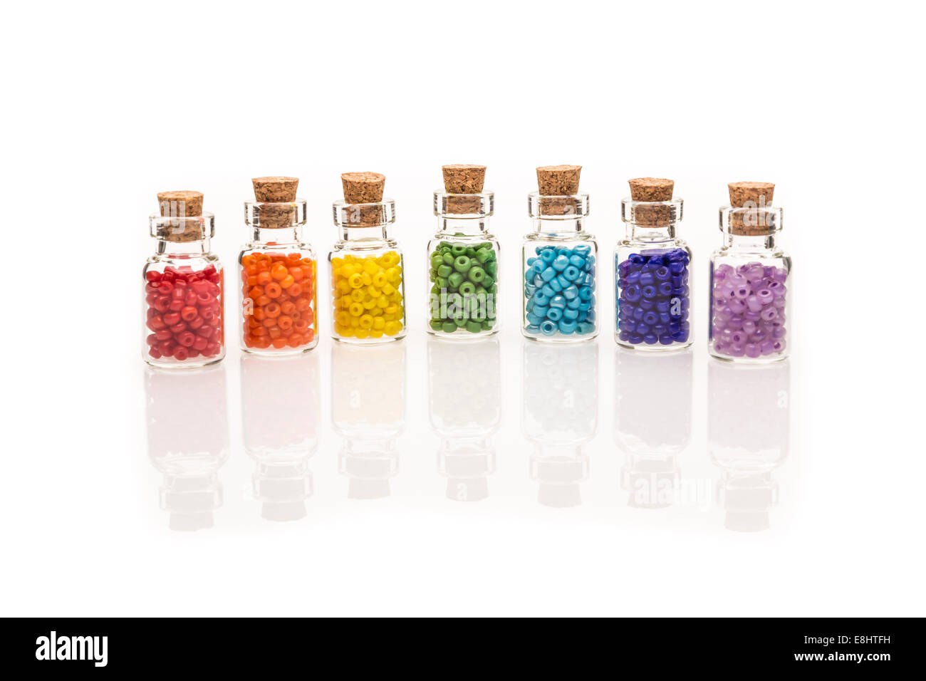 Tiny glass bottles with a cork stopper, filled with a rainbow colours of beads, on a white background Stock Photo