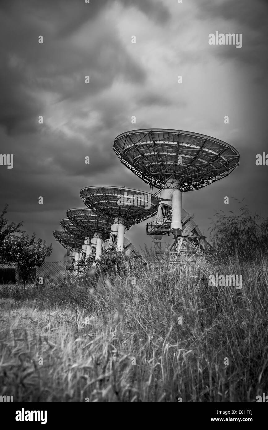 Stormy clouds in the sky, Radio telescope satellite dish array in a barley field in black and white - Stock Image