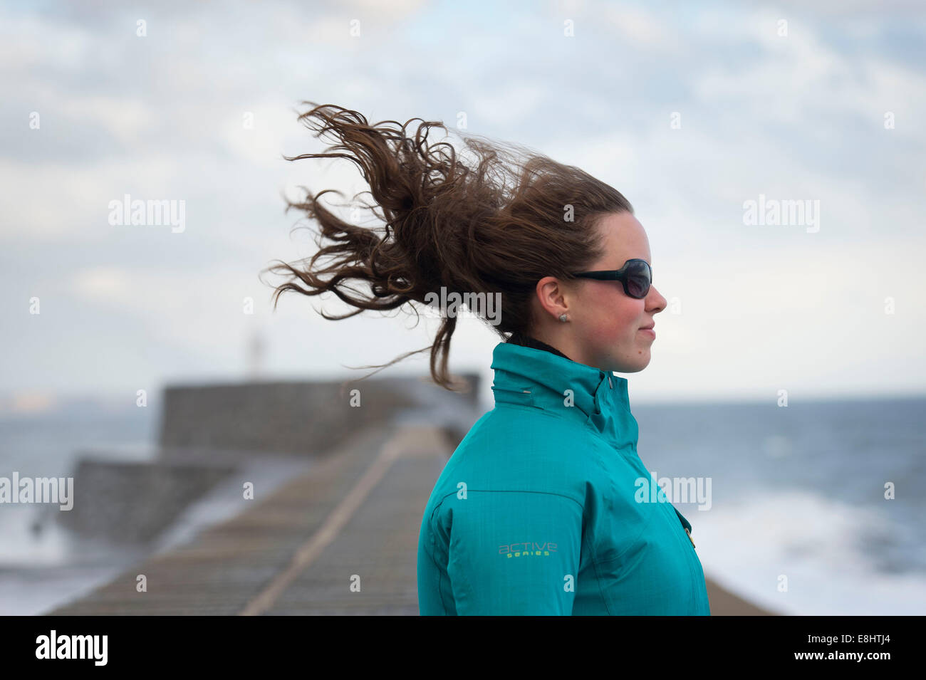 A young female girl stands facing into the wind with her hair blowing behind her. - Stock Image