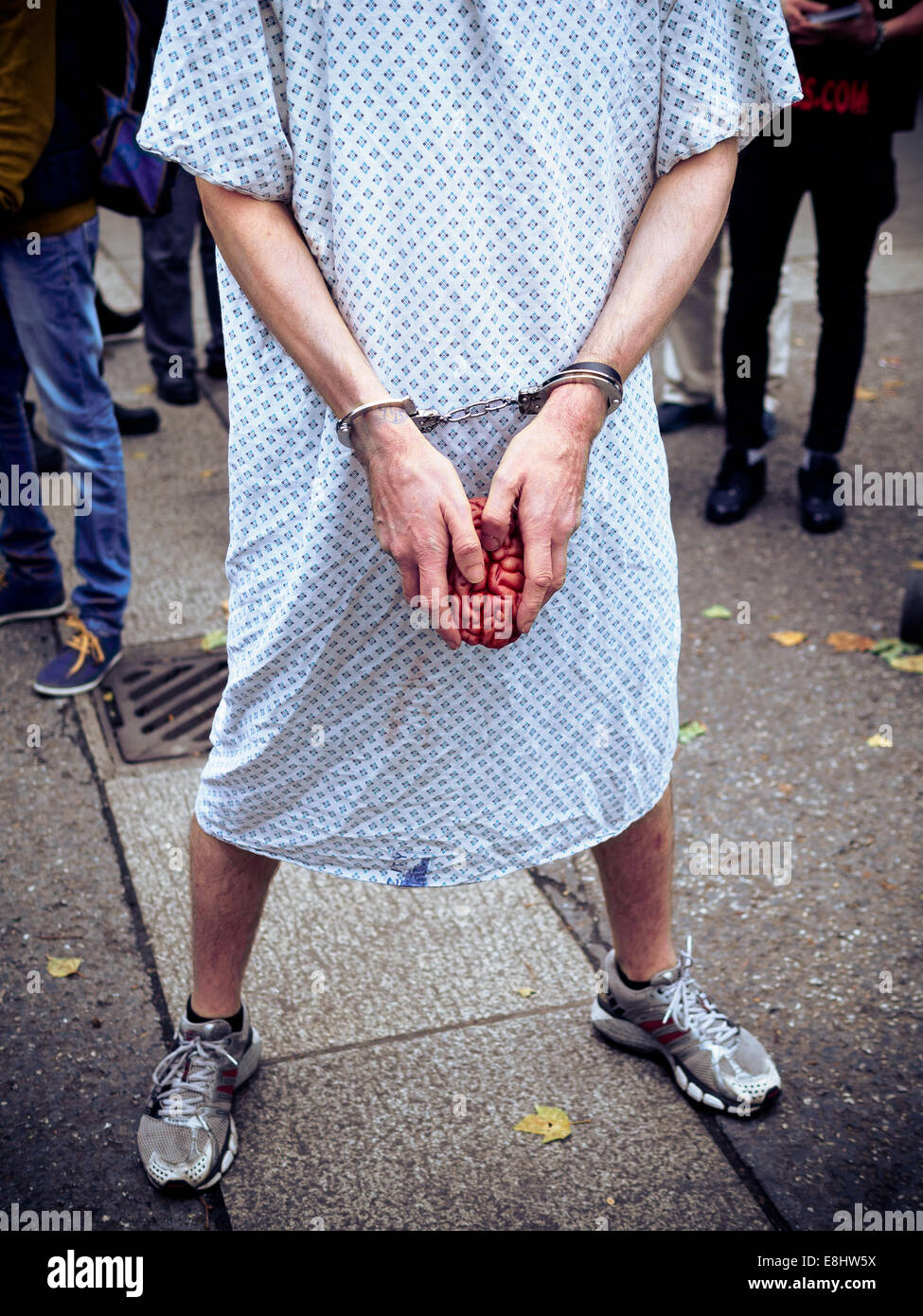 Man in hospital gown with handcuffs holding plastic brain. Head not ...