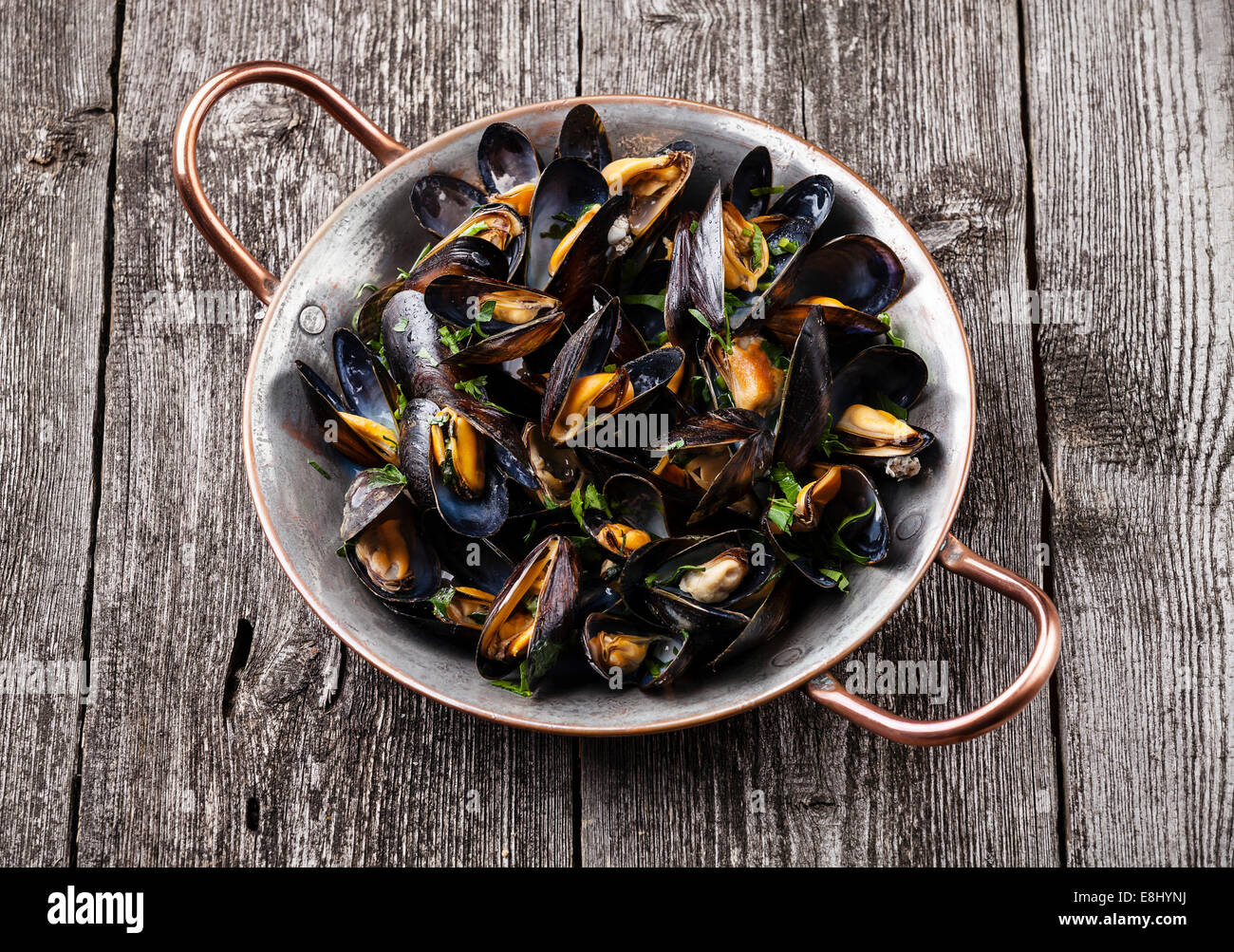 Boiled mussels in copper cooking dish on dark wooden background Stock Photo