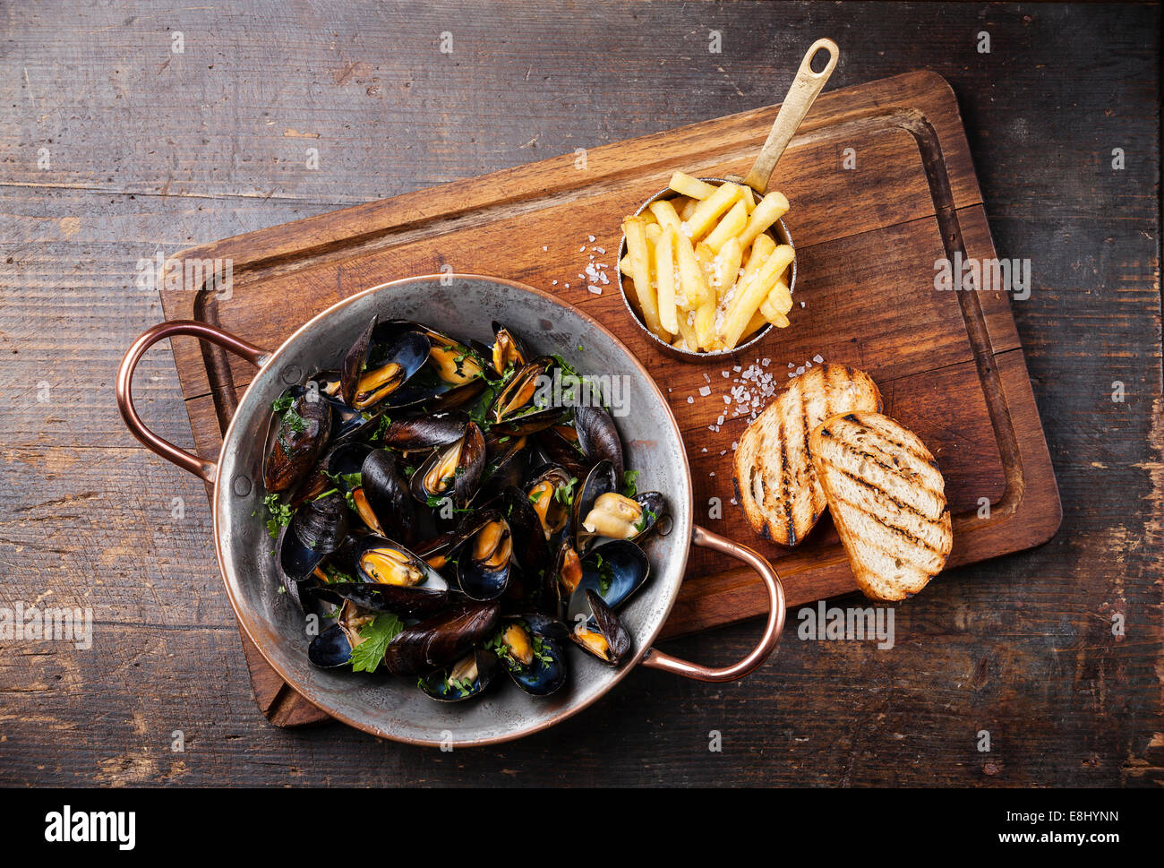 Mussels in copper cooking dish and french fries on dark wooden background - Stock Image