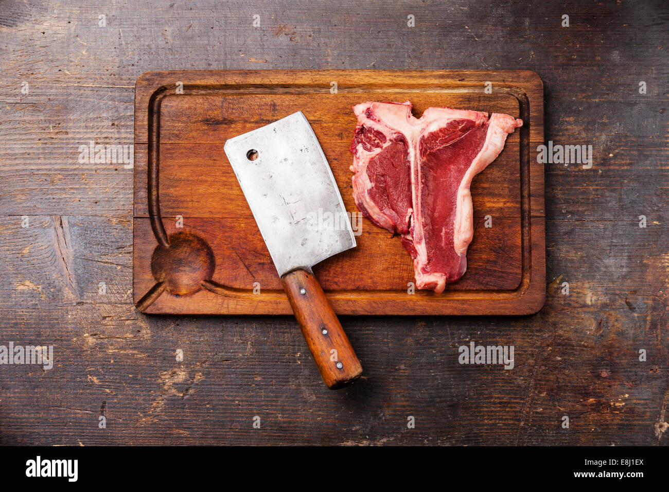 raw fresh meat t bone steak and meat cleaver on cutting board on dark stock photo 74155058 alamy. Black Bedroom Furniture Sets. Home Design Ideas