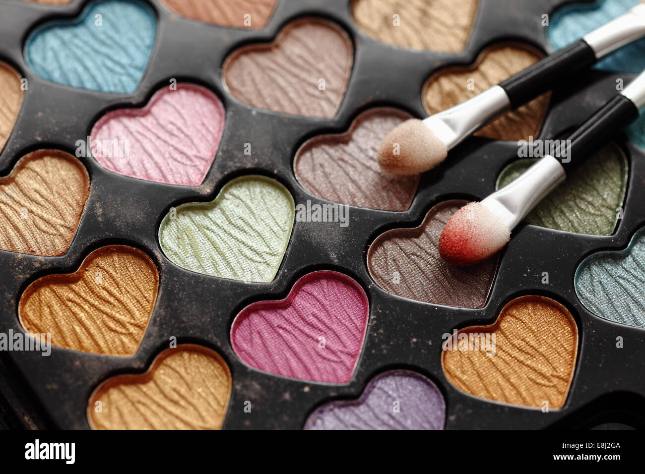 Close-up of eyeshadow heart shaped palette with applicators. - Stock Image