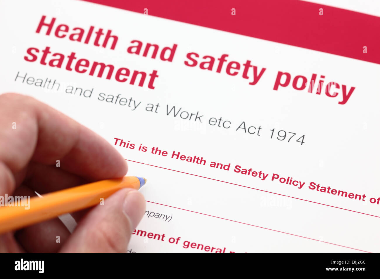 Health and safety policy statement and hand with ballpoint pen. - Stock Image