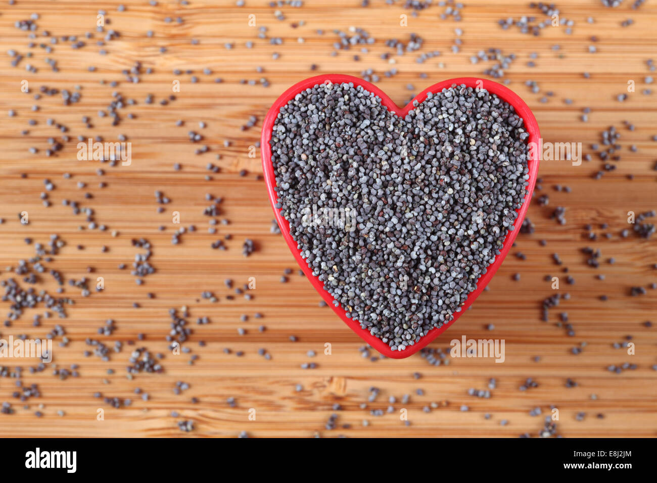 Poppy seeds in a heart bowl. Close-up. - Stock Image