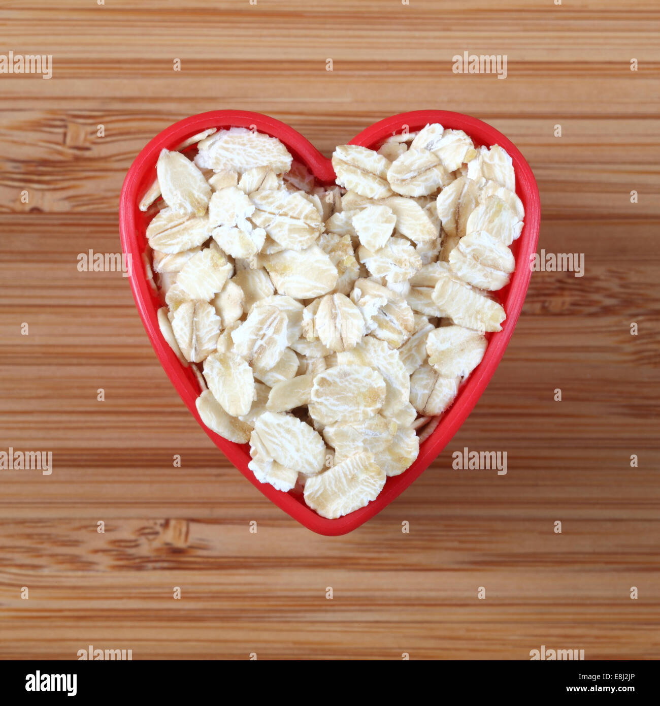 Oatmeal in a heart bowl. Close-up. - Stock Image